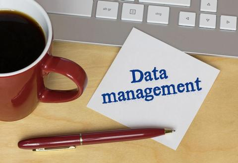 Data Consultants UK And Data Management Specialists. Red cup of coffee and note written on a pad.
